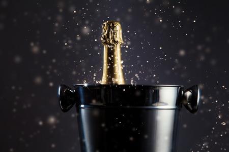 Het concept van de viering. Ongeopende fles champagne in metalen container