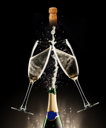 Celebration theme. Glasses and bottle of champagne with bubbles, isolated on black background photo