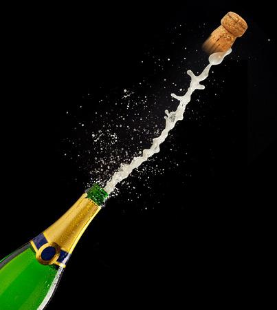 popping cork: Bottle of champagne with splash on black background