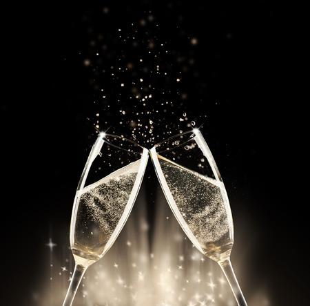 saúde: Dois copos de champanhe com respingo, no fundo preto