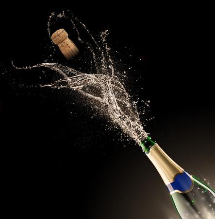 Fles champagne met splash geïsoleerd op zwarte achtergrond