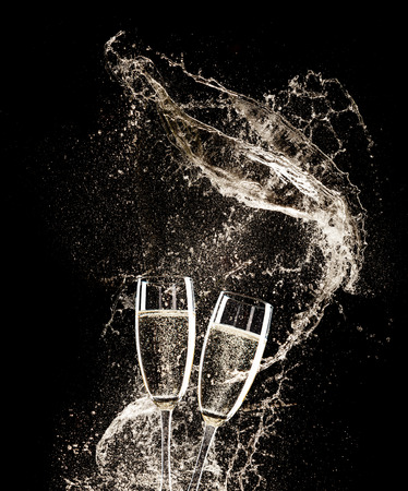 two objects: Glasses of champagne with splash, isolated on black background
