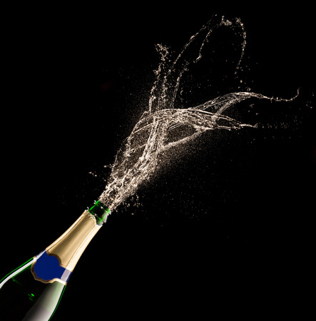 birthday champagne: Bottle of champagne with splash isolated on black background Stock Photo