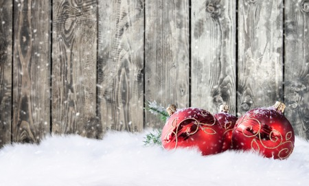 christmas balls: Christmas decorative red balls on snow with wooden planks as background