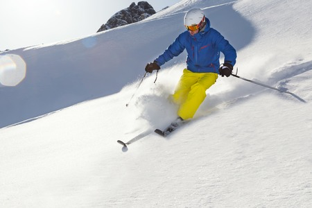 downhill: Male skier on downhill freeride with sun and mountain view