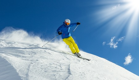 Male skier on downhill freeride with sun and mountain view Stock Photo