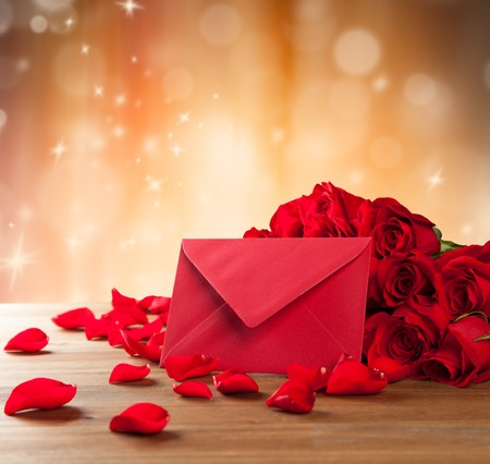 weeding: Bouquet of roses with envelope on wooden desk