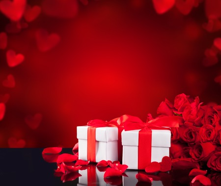 Bouquet of red roses on black glass table with two gifts and abstract blur background with copyspace for text photo