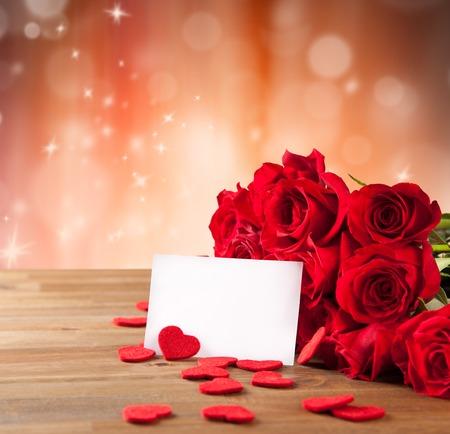 mazzo di fiori: Bouquet di rose rosse sul tavolo in legno con carta bianca in bianco per il testo Archivio Fotografico