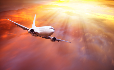jetliner: Passenger airplane flying above clouds in sunset