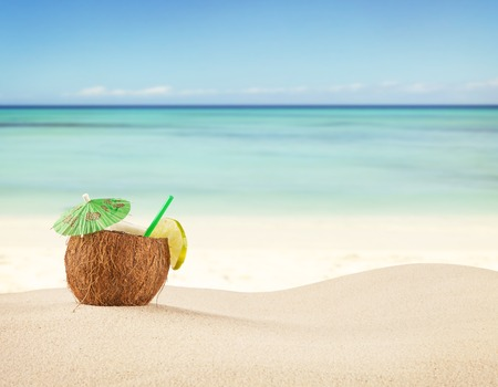 Sandy beach with fresh drink in pineapple fruit