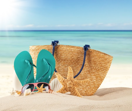 sea shells on beach: Summer concept with sandy beach, shells and blue sandals Stock Photo