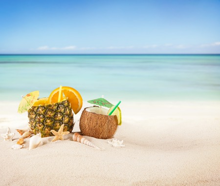 Sandy beach with fresh drinks in pineapple fruit