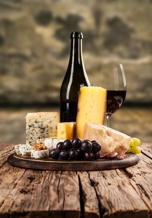 queso: Varios tipos de queso con vino tinto en bodega Foto de archivo
