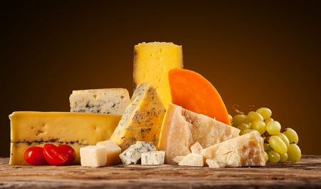 Various kind of cheese served on wooden table