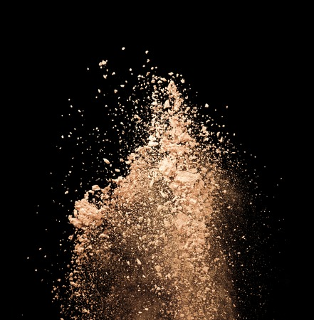 explode: Freeze motion of make-up dust explosion isolated on black background