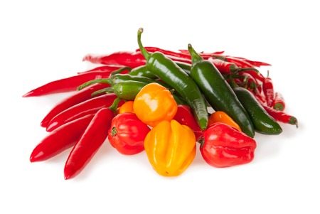 Isolated pile of various kind of chilli peppers isolated on white background