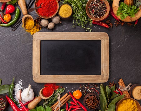 Various spices on black stone with blank blackboard, shot from aerial view photo