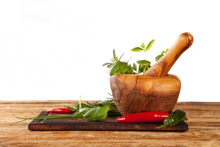 pepper grinder: Wooden mortar filled with fresh herbs, isolated on white background Stock Photo