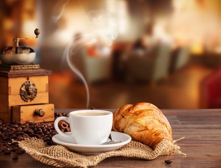 capuchinos: Bebida del café servido con croissant en la mesa de madera con el desenfoque de la cafetería