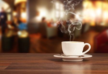 filiżanka kawy: Pić kawę na drewnianym stole z rozmycia stołówce Zdjęcie Seryjne
