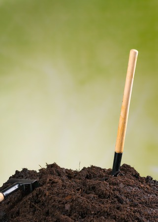 molehill: Pile of soil with gardening tools on green