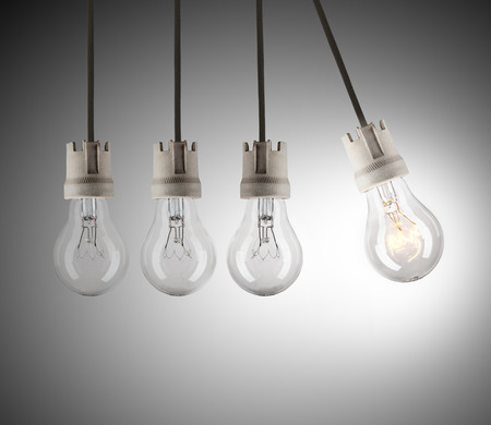 shinning light: Light bulbs in row with single one in motion and shinning