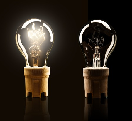 idea lamp: Light bulbs switched on and off, isolated on black background
