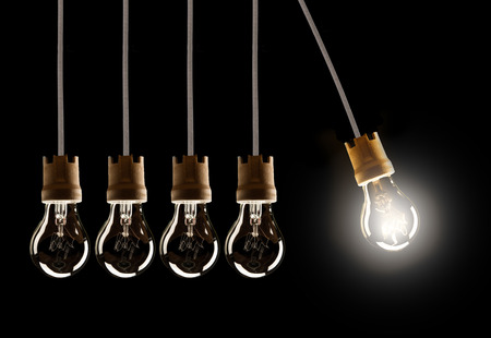 Light bulbs in row with single one in motion and shinning, isolated on black background Stock Photo