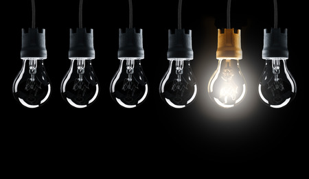 Light bulbs in row with single one shinning, isolated on black background