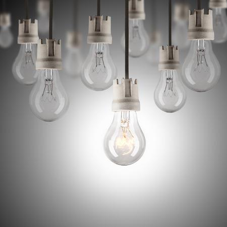 shinning: hanging light bulbs with single one shinning Stock Photo