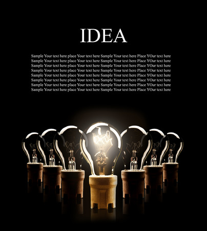 shinning light: Light bulbs in rows with single one shinning, isolated on black background