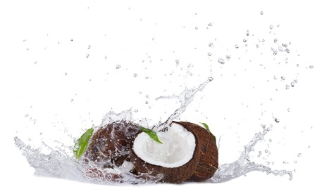 Isolated shot of cracked coconuts with water splash on white background Stock Photo
