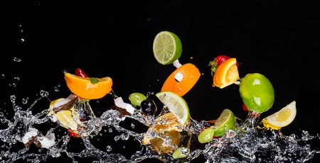 leaf water drop: Mix of fruit with water splashes isolated on black background Stock Photo
