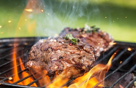 barbecue fire: Beef steaks on grill Stock Photo