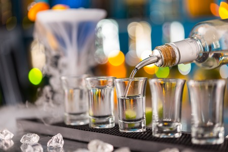 shooter drink: Barman pouring hard spirit into glasses in detail