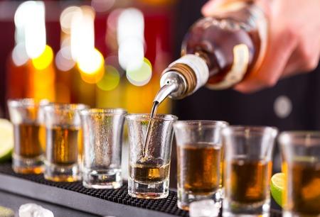 tomando alcohol: Barman verter esp�ritu duro en gafas en detalle