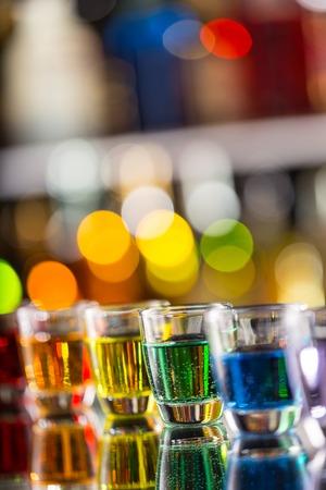 rainbow cocktail: Variaci�n de disparos alcoh�licas duros servido en barra de bar. Botellas de Blur en el fondo Foto de archivo