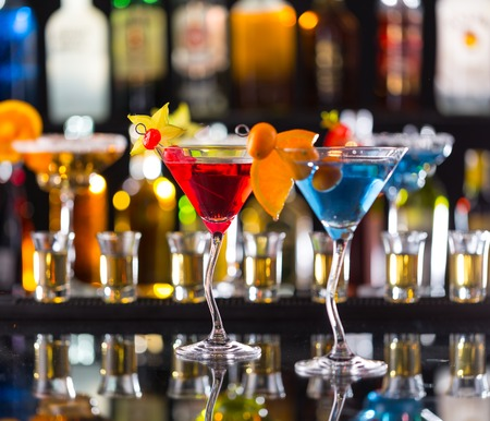 night stick: Martini drinks served on bar counter with blur bottles on background