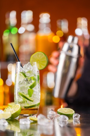 Mojito cocktail drink on bar counter with barman holding shaker on background photo