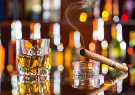 bar counter: Whiskey drink with smoking cigar on bar counter
