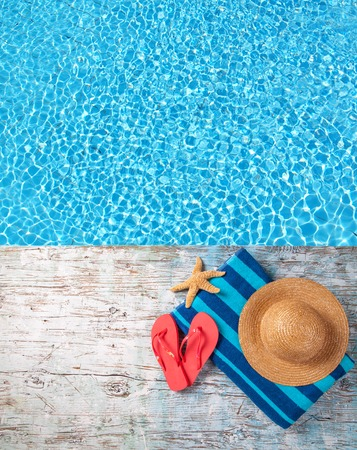 birdeye: Swimming accessories on wooden mole placed next to water surface of pool. Shot from bird-eye perspective Stock Photo