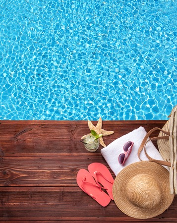 pool deck: Swimming accessories on wooden mole placed next to water surface of pool. Shot from bird-eye perspective Stock Photo