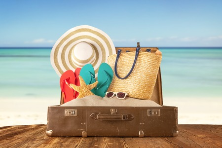 baggage: Travel concept with old suitcase on wooden planks full of beach accessories. Placed on mole with sandy beach on background Stock Photo