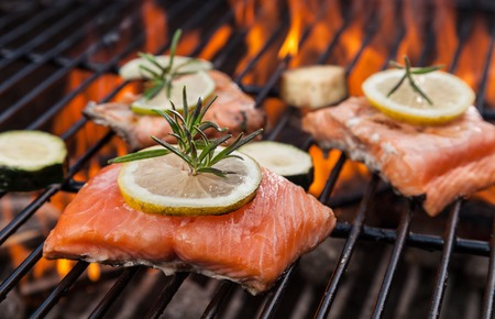 barbecue fire: Delicious grilled salmon steaks on fire Stock Photo