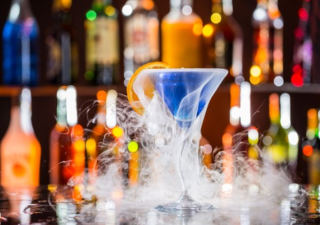 bar counters: Martini drink with dry ice smoke effect, served on bar counter with blur bottles on background