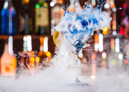 Martini drink with dry ice smoke effect and splash, served on bar counter with blur bottles on background