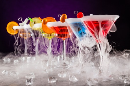 nightclub: Martini drinks with dry ice smoke effect, served on bar counter with dark colored background Stock Photo