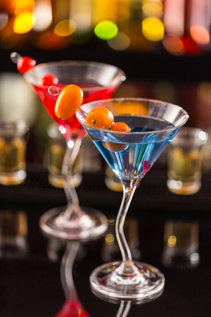 vertical bars: Martini drinks served on bar counter with blur bottles on background