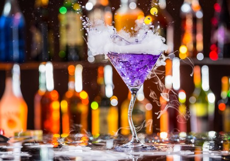 nightclub: Martini drink with dry ice smoke effect and splash, served on bar counter with blur bottles on background
